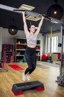 Женщина делает прыжки упражнения с баром в тренажерном зале — стоковое фото