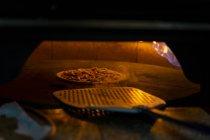 Poner una pizza con cáscara de pizza en el horno - foto de stock