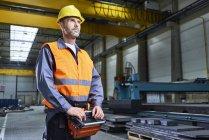 Retrato del hombre en la maquinaria de operación de fábrica con consola remota - foto de stock