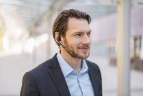 Retrato de homem de negócios sorrindo usando fone de ouvido ao ar livre — Fotografia de Stock