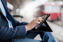 Primer plano del hombre de negocios en la estación utilizando la tableta - foto de stock