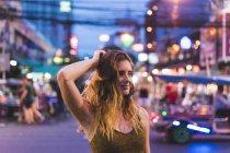 Таїланд, Бангкок, молода жінка в місті на вулиці вночі — стокове фото