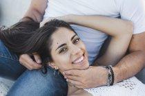 Jovem feliz deitado no colo do namorado, retrato — Fotografia de Stock