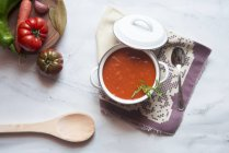 Cooking pot of homemade tomato soup on marble — Stock Photo