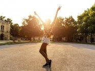 Mulher nova na moda feliz com fones de ouvido dançando ao ar livre ao pôr do sol — Fotografia de Stock