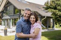Портрет счастливой пары в саду своего дома — стоковое фото