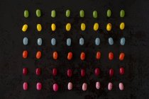 Arreglo de caramelos de colores en el suelo negro - foto de stock