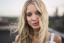 Portrait of smiling blond young woman looking at camera, windy weather — Stock Photo