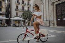 Jovem elegante explorando Barcelona com bicicleta, usando smartphone — Fotografia de Stock