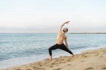Spanien. Mann macht abends Yoga am Strand — Stockfoto