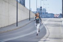 Female runner during urban workout — Stock Photo
