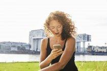 Allemagne, Cologne, portrait d'une jeune femme sérieuse utilisant un téléphone portable au bord de la rivière — Photo de stock