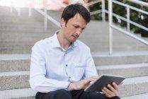Empresário sentado nas escadas usando tablet — Fotografia de Stock