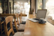 Laptop with blank screen in coffee shop — Stock Photo