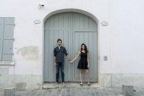 Jeune couple debout main dans la main devant le bâtiment — Photo de stock