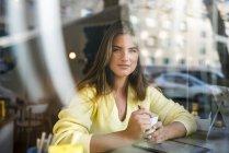 Retrato de jovem sorridente em um café — Fotografia de Stock