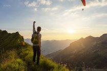 Homme randonnée dans les montagnes au coucher du soleil, main en l'air — Photo de stock