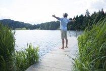 Германия, Миттенвальд, зрелый мужчина, стоящий с распростертыми руками на причале у озера — стоковое фото