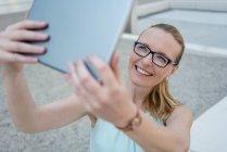 Портрет усміхнена жінка в окулярах беручи селфі з планшетом — стокове фото
