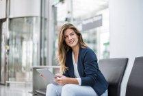 Giovane donna d'affari seduta in sala d'attesa utilizzando tablet — Foto stock