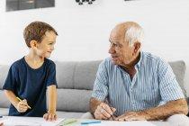 Дедушка и внук рисуют вместе с цветными карандашами дома — стоковое фото