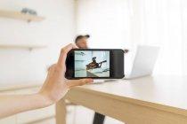 Mano con cellulare scattare foto di uomo che suona la chitarra a casa — Foto stock