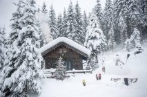 Austria, Altenmarkt-Zauchensee, snowman, sledges and Christmas tree at wooden house in snow — Stock Photo