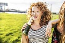 Германия, Кельн, портрет рыжеволосой молодой женщины, наслаждающейся напитком — стоковое фото