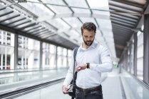 Young businessman on moving walkway checking the time — Stock Photo