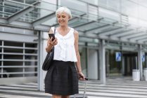 Smiling senior woman with baggage using cell phone — Stock Photo