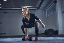 Женщина делает гантели упражнения в спортзале — стоковое фото