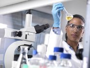 Biotechnology Research, female scientist mixing a chemical formula — Stock Photo