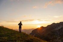 Homem caminhando em montanhas ao pôr do sol — Fotografia de Stock