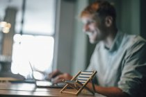 Jeune homme utilisant un ordinateur portable avec petit transat au premier plan — Photo de stock