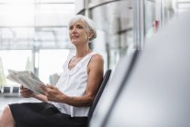 Senior woman sitting in waiting area with newspaper — Stock Photo