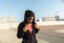 Jovem mulher esportiva ouvindo música com fones de ouvido — Fotografia de Stock