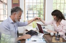 Mature couple high fiving in home office, using laptop and digital tablet — Stock Photo