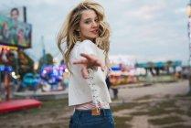 Блондинка молода жінка веселяться в Луна-парк, дивлячись на камеру і дати руку — стокове фото