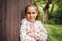 Portrait of smiling girl leaning against wooden wall — Stock Photo