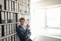 Empresário no arquivo da empresa, encostado à prateleira com arquivos — Fotografia de Stock