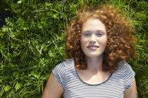 Портрет улыбающейся молодой женщины, лежащей на зеленом лугу — стоковое фото