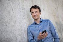 Portrait d'homme d'affaires souriant avec téléphone portable appuyé contre un mur en béton — Photo de stock