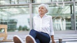 Mulher de negócios sênior sorridente sentada na frente do edifício de vidro — Fotografia de Stock