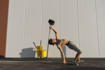 Acrobat playing with cleaning bucket and mop — Stock Photo