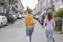 Two female friends running in city — Stock Photo
