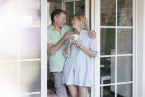 Glückliches reifes Paar steht am französischen Fenster — Stockfoto