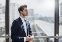 Businessman at the window looking around — Stock Photo