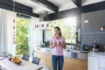 Lachende Frau zu Hause in der Küche mit Tasse Kaffee — Stockfoto