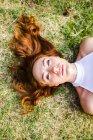 Портрет рыжеволосой девушки, лежащей на лугу — стоковое фото
