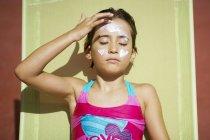 Little girl in swimwear putting on suncream on face — Stock Photo